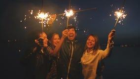 Группа в составе молодые друзья имея партию пляжа Друзья танцуя и празднуя с бенгальскими огнями в twilight заходе солнца акции видеоматериалы