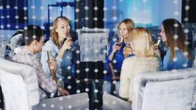 Группа в составе молодые друзья ослабляя в кафе или клубе Сидящ на таблице, шампанском питья или бокалах акции видеоматериалы