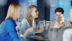Группа в составе молодые друзья ослабляя в кафе Полезного время работы, obschayutsya, выпивая вино, наслаждается вашим smartphone сток-видео