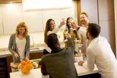 Группа в составе молодые друзья провозглашать с белым вином стоковые фото