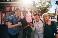 Группа в составе молодые друзья с конфетой хлопка в парке атракционов Стоковые Изображения RF