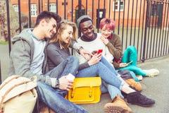 Группа в составе молодые друзья с умными телефонами Стоковое Фото