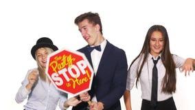 Группа в составе молодые друзья танцуя и держа партия здесь знак - съемка студии акции видеоматериалы