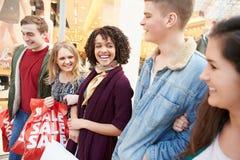 Группа в составе молодые друзья ходя по магазинам в моле совместно Стоковое фото RF