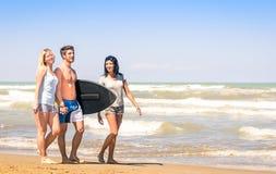 Группа в составе молодые счастливые друзья с surfboard на пляже Стоковая Фотография RF
