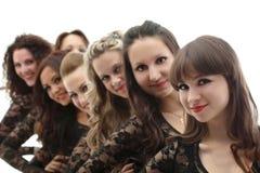 Группа в составе молодые усмехаясь девушки представляя в студии Стоковая Фотография