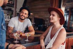 Группа в составе молодые люди встречая в кафе Стоковая Фотография