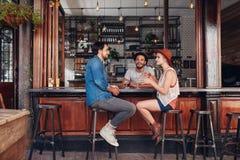 Группа в составе молодые люди встречая в кофейне Стоковое Фото