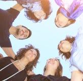 Группа в составе молодые люди в круге на небе смотря один другого Стоковое Изображение