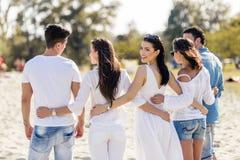 Группа в составе молодые люди держа руки на пляже Стоковые Изображения RF
