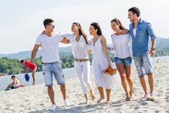 Группа в составе молодые люди держа руки на пляже Стоковое фото RF