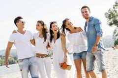 Группа в составе молодые люди держа руки на пляже Стоковое Фото