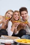 Группа в составе молодые люди есть пиццу дома Стоковые Фотографии RF