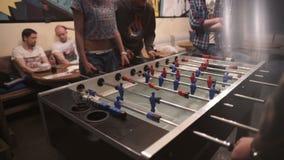 Группа в составе молодые люди играя футбол таблицы в баре видеоматериал