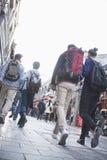 Группа в составе молодые люди идя вниз с оживленной улицы, вид сзади. Стоковые Фото