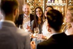 Группа в составе молодые люди празднуя и провозглашать с белым вином Стоковое Фото