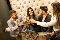 Группа в составе молодые люди празднуя и провозглашать с белым вином Стоковая Фотография