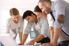 Группа в составе молодые люди работая на офисе Стоковые Изображения