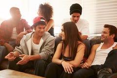 Группа в составе молодые люди сидя на софе и говорить стоковое изображение