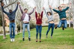 Группа в составе молодые люди скача совместно outdoors Стоковое Изображение RF