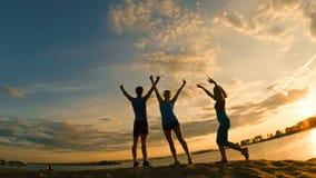 Группа в составе молодые люди - спортсмены - 2 девушки и парень имеет триумф на горе, около реки на сумраке Стоковая Фотография