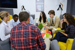 Группа в составе молодые люди, Startup предприниматели работая на их рискованом начинании в coworking космосе Стоковые Изображения