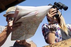 Группа в составе молодые hikers смотря карту Стоковая Фотография
