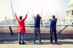Группа в составе 3 молодых друз поднимает их оружия стоковое фото rf