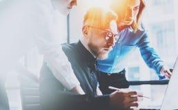 Группа в составе 3 молодых сотрудника работая совместно на современном coworking офисе Принципиальная схема сыгранности запачканн Стоковые Изображения RF
