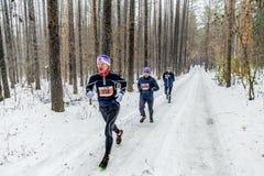 группа в составе мужские бегуны бежать снежный лес, снег падает Стоковое фото RF
