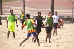 Группа в составе мужские и женские подростки играя футбол на пляже Стоковая Фотография