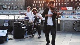 Группа в составе музыканты играя на крымском обваловке в Москве в вечере лета сток-видео