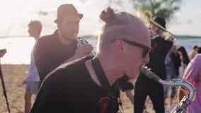 Группа в составе музыканты парней выполняет на солнечном пляже лета среди много людей видеоматериал