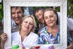 Группа в составе обнимая жизнерадостные активные старшии имея потеху во время партии задворк Стоковая Фотография