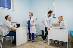 Группа в составе обсуждение докторов Включенн В серьезное с медицинскими историями Стоковое фото RF