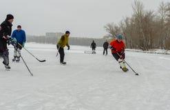 Группа в составе обычные люди играя hokey на замороженном реке Dnipro в Украине стоковое изображение