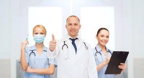Группа в составе доктора на больнице показывая большие пальцы руки вверх Стоковое Изображение