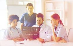 Группа в составе доктора обсуждая изображение рентгеновского снимка Стоковая Фотография