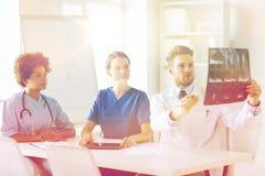 Группа в составе доктора обсуждая изображение рентгеновского снимка Стоковые Фото
