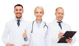 Группа в составе доктора показывая большие пальцы руки вверх над белизной Стоковые Фотографии RF