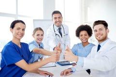 Группа в составе доктора показывая большие пальцы руки вверх на больнице Стоковые Фото