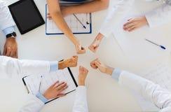 Группа в составе доктора показывая большие пальцы руки вверх над таблицей Стоковые Изображения