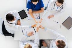 Группа в составе доктора показывая большие пальцы руки вверх над таблицей Стоковое Фото
