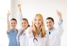 Группа в составе доктора показывая большие пальцы руки вверх Стоковые Фото