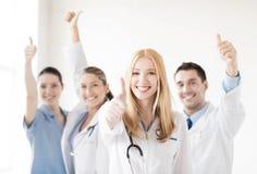 Группа в составе доктора показывая большие пальцы руки вверх Стоковые Изображения