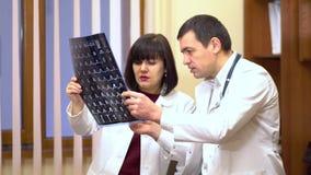 Группа в составе доктора рассматривает рентгеновский снимок Женщины и человек Они водят обсуждение видеоматериал