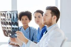 Группа в составе доктора смотря к рентгеновскому снимку на больнице Стоковые Изображения RF