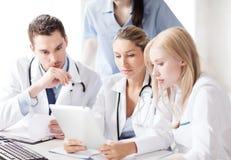 Группа в составе доктора смотря ПК таблетки Стоковая Фотография