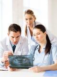 Группа в составе доктора смотря рентгеновский снимок Стоковая Фотография RF