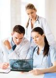 Группа в составе доктора смотря рентгеновский снимок Стоковое фото RF